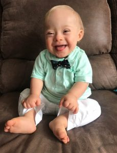 Photo of 1 year old Lucas Warren, the winner of Gerber's annual baby photo contest. Lucas has Down syndrome. Lucas wears a light green shirt, white pants, and a blue bowtie. He smiles cheerfully into the camera.