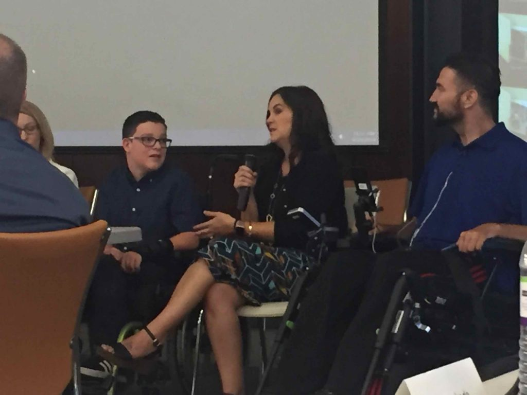 Tessa Ringo, a brunette woman in a blue dress, and her adolescent son Aiden, who has brunette hair and glasses and uses a wheelchair, describe their experiences discussing disabilities with acquaintances and reporters. They sit amongst a row of panelists and Tessa holds a portable microphone near her mouth.