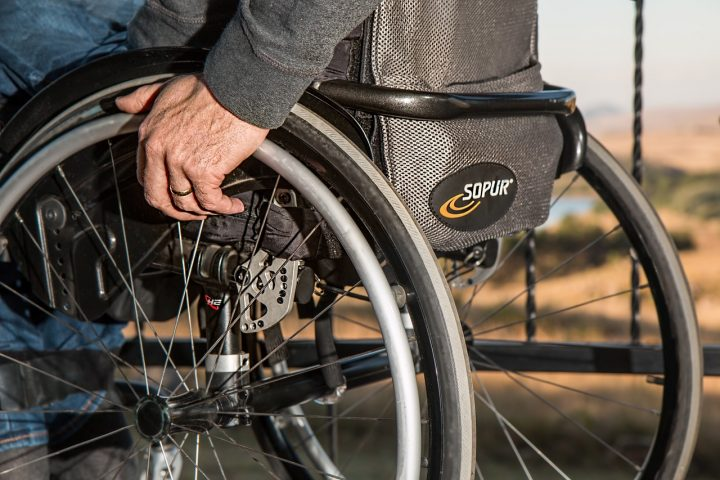 Image shows a hand holding onto the rim of a wheelchair.