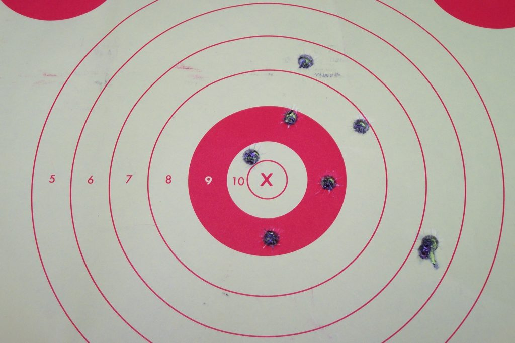 The image depicts a paper gun range shooting target with several bullet holes. (Image: Wikimedia)