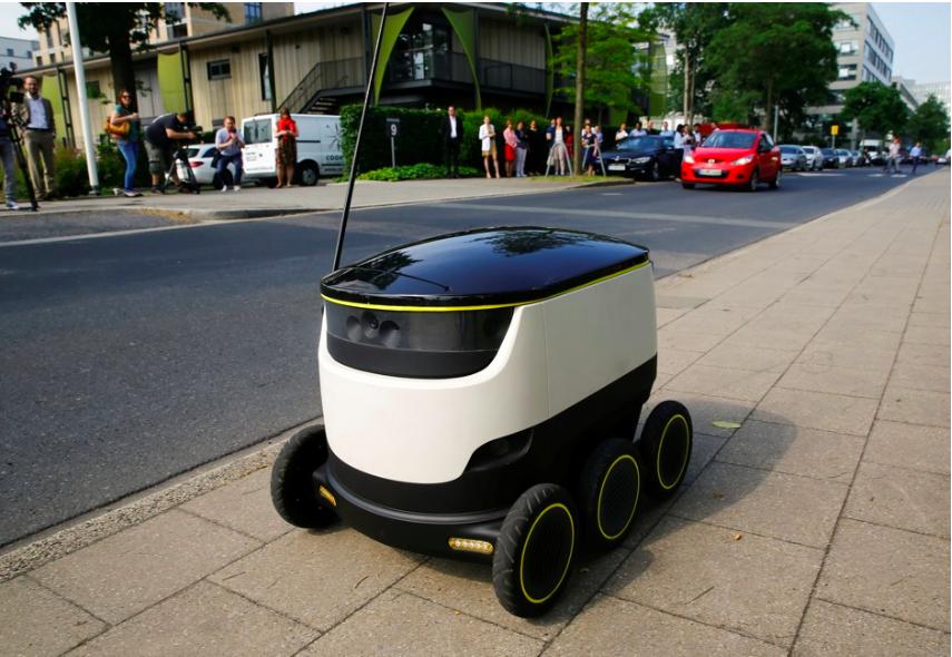 A mid-sized robot on a sidewalk
