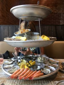 Photo of Hannah Raskin hiding behind a tall seafood platter.