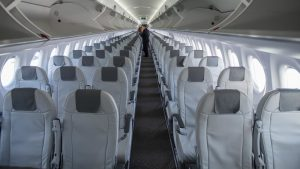 A mostly empty airplane with people beginning to fill in.